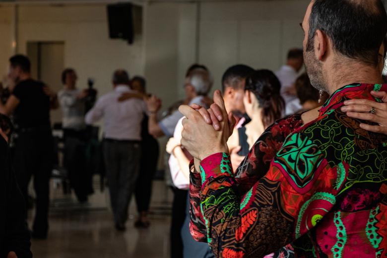 tango dansende paren, op de achtergrond enkele in de schaduw, halverwege een paar in wit en zwart; door het invallende zonlicht belicht , en op de voorgrond de rug van een paar in bonte kleuren rood, zwart en groen